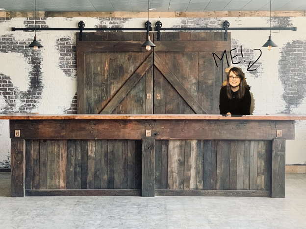 The tasting room bar made of upcycled pallet wood with Wine Shop Manager Michelle photoshopped into the photo.