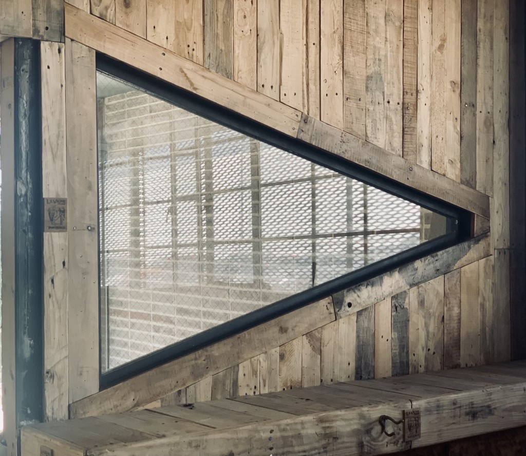 A tringle-shaped window framed and surrounded by upcycled pallet wood.