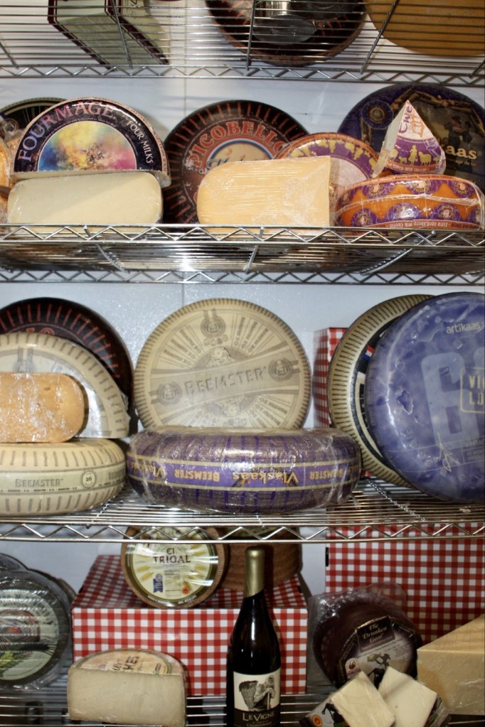 Three shelves with cheese wheels and wedges.