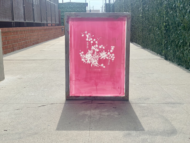 Screen printing frame with flower design on a hot pink background.
